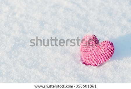 The knitting heart on a snowy background. Greeting card for Valentine's Day