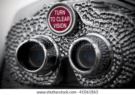 The knob that reads turn to clear vision, on pay binoculars. Closeup view and slightly desaturated image. - stock photo