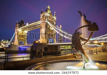 The lady and the dolphin fountain with Tower Bridge at night, London, UK - stock photo