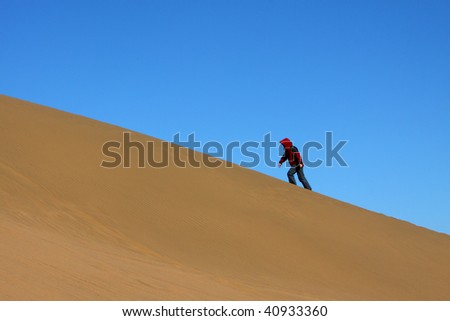 The lady in red is ascending the sand hill in Ba Dan Ji Lin desert, Inner Mongolia, China - stock photo