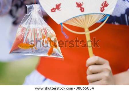 The lady who wears white and a blue yukata and goldfish in a festival day.
