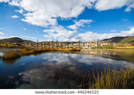 The lake and temple in blue sky background, Shangri-la County, Yunnan Province, China - stock photo