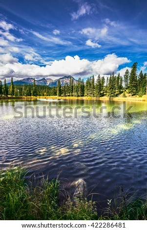 The lake is surrounded by evergreen firs. Small lake in the Rocky Mountains of Canada - stock photo