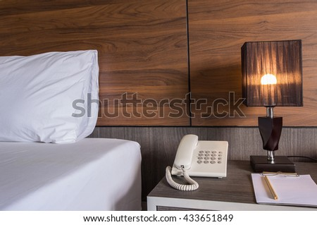The lamp on the table next to the bed, and telephone.