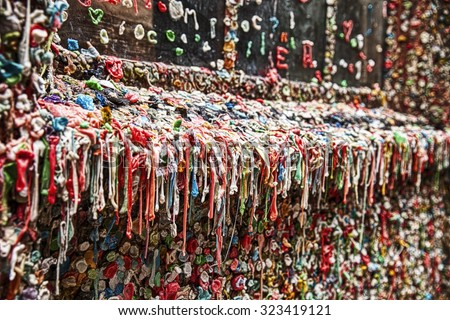 The landmark bubble gum wall near the Pike Place Market in Seattle is a dirty, unhygienic wall filled with half-chewed bubble gum that is dripping from every surface. - stock photo