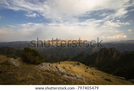 The landscape. autumn mountain canyon with cloudy sky and birch forest.
