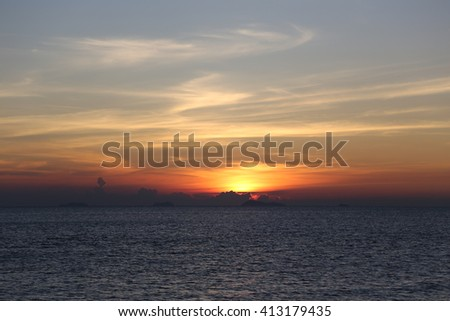 The landscape photography of orange sun setting into the ocean in the sea on koh samui Thailand