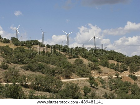 The landscape with white wind turbines on the mountain with treed slopes and the earth road. This photo was taken on the Meganom cape in Crimea.