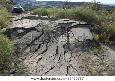 the landslide of a rural road on the background an off-road car - stock photo