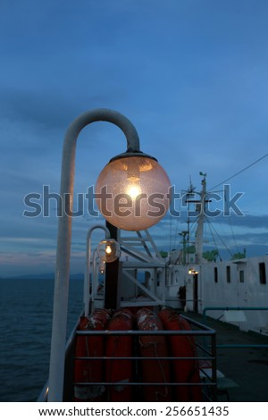 The lantern on the ferry on the background of blue sky and sunset