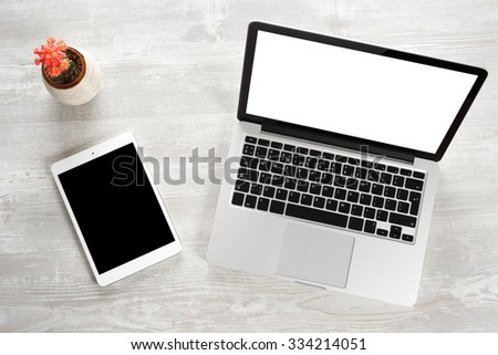 The laptop with the notepad on the desk in the office - stock photo