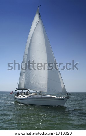 The large beautiful yacht with white sails on a background of the brightly light-blue clean sky and quiet sea. - stock photo