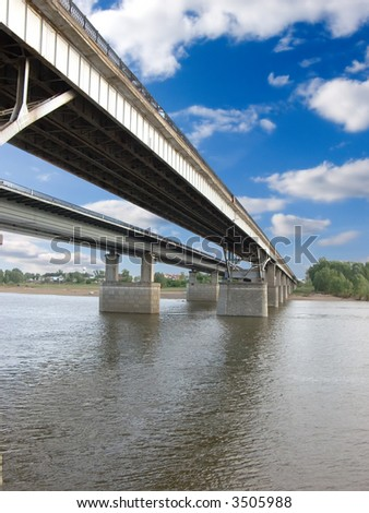 The large bridge through the river. The photo is created in the Russian province in the summer.