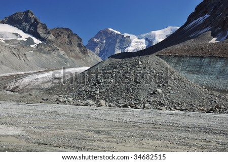 the large glacier on the left has recently retreated exposing a flat valley floor and ice cliff with glacial debris. Global warming is causing glaciers to melt and sea levels to rise - stock photo