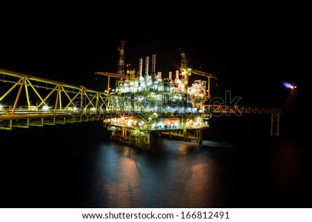 The large offshore oil rig at night with twilight background - stock photo
