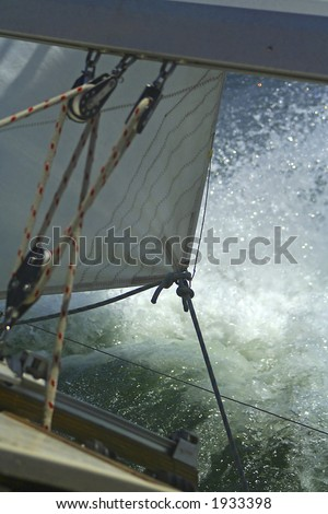 The large waves cover a sailing yacht. Sails and rigging. - stock photo
