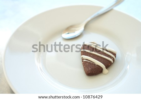 The last cookie on a white ceramic plate with a silver teaspoon - Shallow Depth of Field, focus on the tip of the cookie