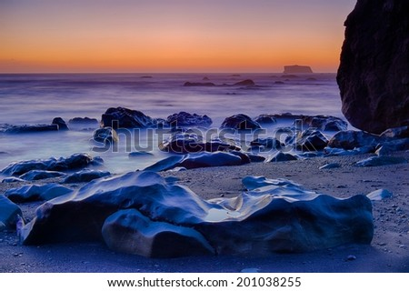 The last light of day glows on wet rocks at Rialto Beach in Olympic National Park, Washington, USA - stock photo