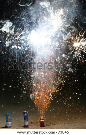 The last of the fireworks from the Fourth of July, being set off in the driveway. - stock photo