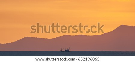 The last of the setting sun over Ko Chang island, east Thailand. A small fishing boat passes.