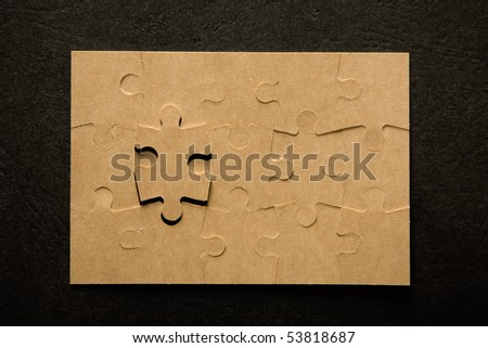 The last piece of a puzzle game, details on black background - stock photo