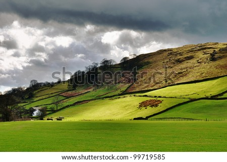 The last rays of sunlight light up the lush green farmland under ominous gathering storm clouds in Longsleddale, English Lake District - stock photo