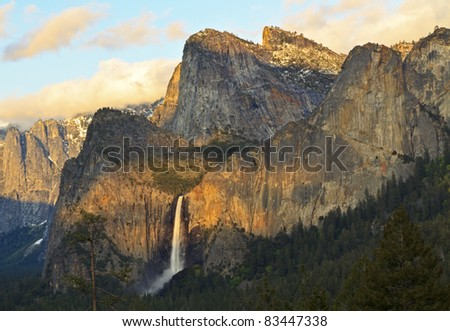 The last rays of sunset splash Cathedral Rocks around Bridalveil Falls in Yosemite National Park, California - stock photo