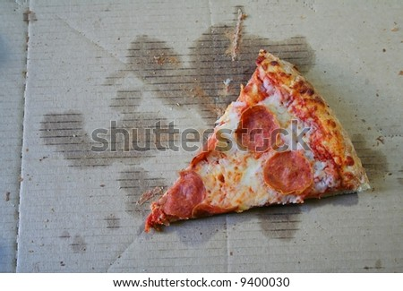 The last slice of pepperoni pizza in a box. - stock photo