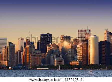 The last sun beams of the day reflect on the glass skyscrapers of Manhattan - stock photo