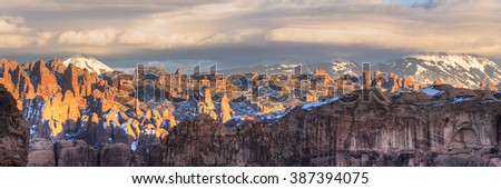 The last sunlight hits the sandstone fine in the Behind the Rocks Wilderness area with the La Sal Mountains behind in Moab, Utah - stock photo