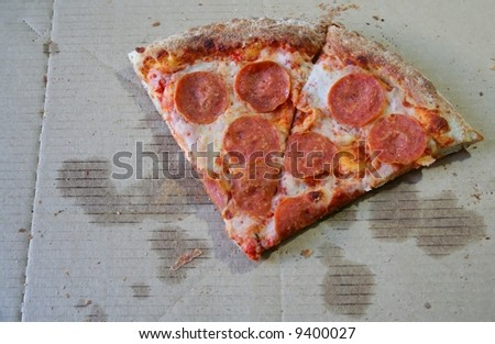 The last two slices of pepperoni pizza in a box. - stock photo