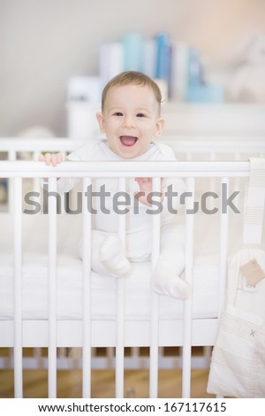 The laughing baby in a cot at home - baby in bed