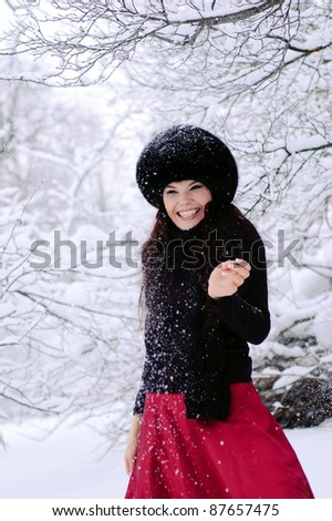 The laughing woman stands under falling snow.