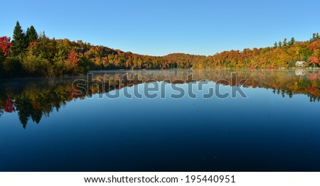 The Laurentian forest in the fall with reflections in a lake, Quebec, Canada - stock photo