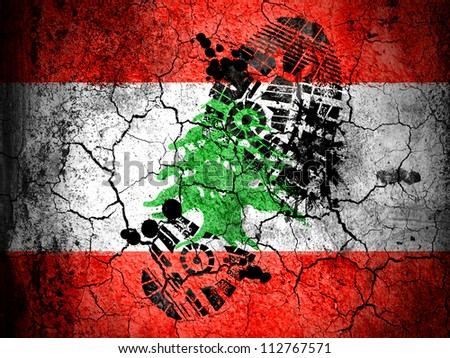 The Lebanese flag painted on cracked ground with vignette with dirty oil footprint over it - stock photo