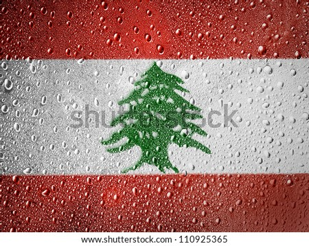 The Lebanese flag painted on metal surface covered with rain drops - stock photo