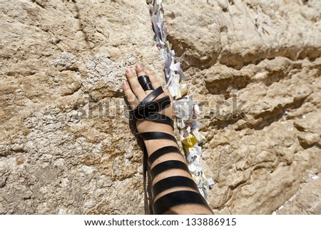 The left hand of a Jewish adult (early 30's) Caucasian man wrapped with Phylacteries, resting on the holy Western Wall (aka Wailing Wall) in the old city of Jerusalem, Israel. - stock photo