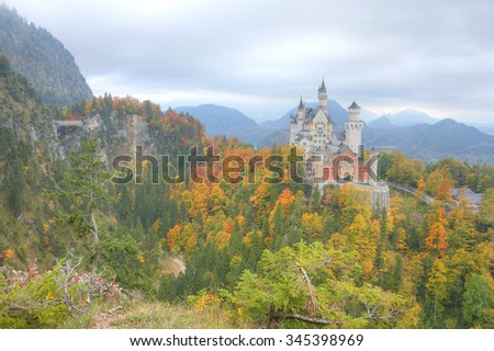 The legendary new swan stone castle perched high on a cliff surrounded with colorful autumn foliage in Fussen, Bavaria, Germany ~ Magnificent scenery of a beautiful castle on a mountaintop - stock photo