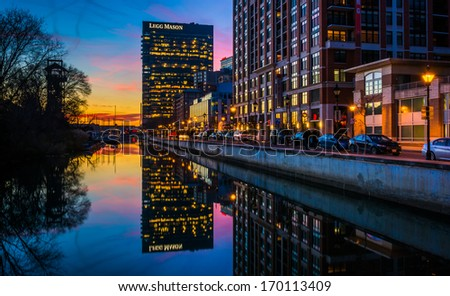 The Legg Mason Building reflecting in the water at twilight, in Harbor East, Baltimore, Maryland. - stock photo