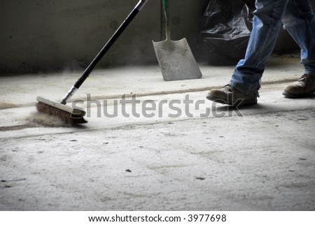 The legs and feet of a construction worker sweeping up on rough concrete at a job site using a large broom - stock photo