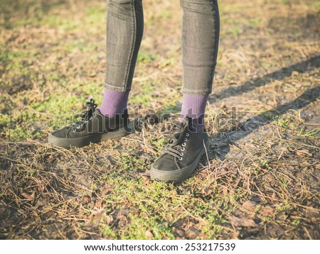 The legs and feet of a person standing on the grass in the park