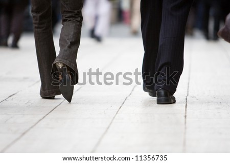 The legs of a business man and woman walking away from the camera - stock photo