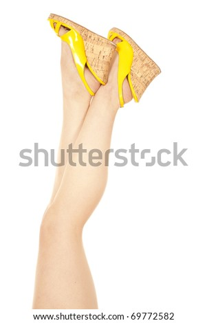 The legs of a woman in yellow shoes up in the air. - stock photo