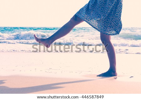 The legs of a woman walking on the beach, retro style. - stock photo