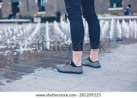 The legs of a young woman as she is standing by a small fountain in the city
