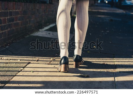 The legs of a young woman as she is walking in the street