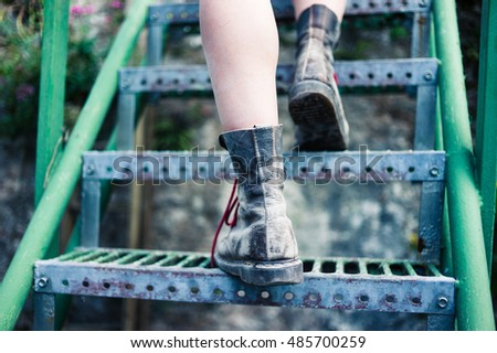 The legs of a young woman as she is walking up some stairs outside