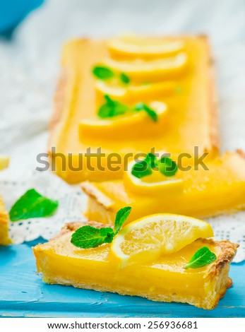the lemon cream pie cut on pieces and decorated with fresh mint. selective focus. - stock photo