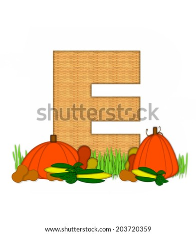 "The letter E, in the alphabet set ""Blessed Bounty"", is filled with wicker texture.  Letter sits in grassy field surrounded by Fall vegetables. - stock photo"