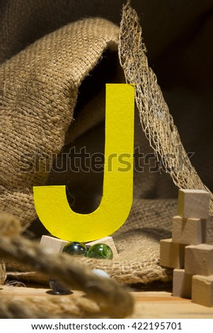 "The letter "" J "" by  Photo font "" Yellow Texture "" and subjects with active texture. Wood, burlap, glass beads. Preparation for graphic design"